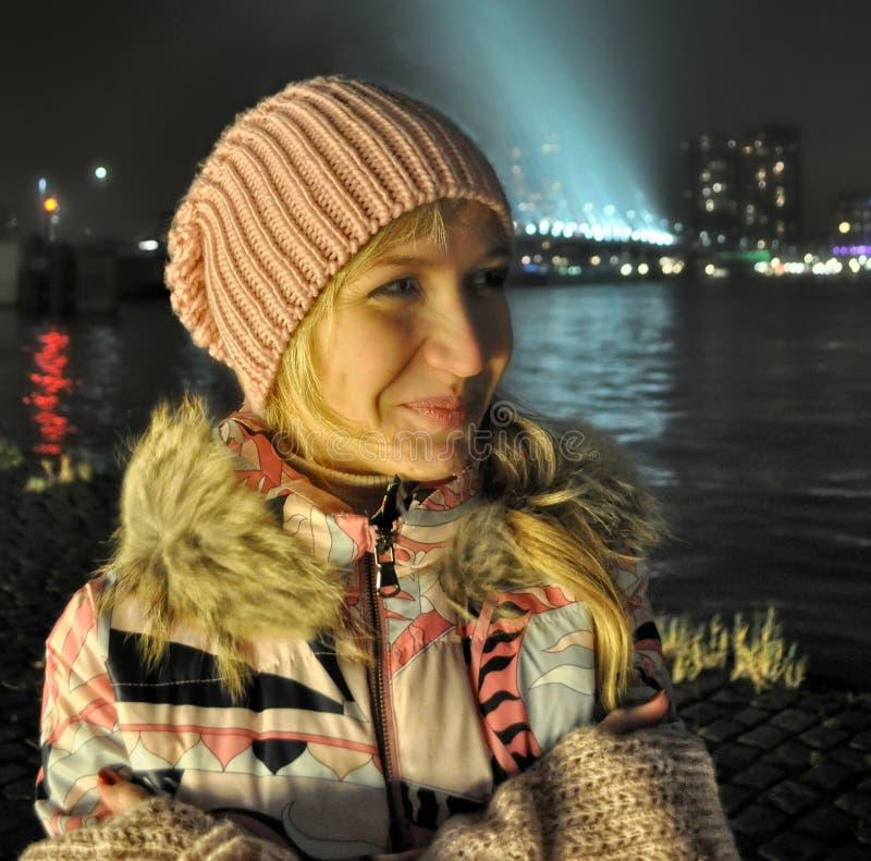 Fille de sourire dans la veste rose au centre d'Amsterdam la soirée bleue d'heure photo stock
