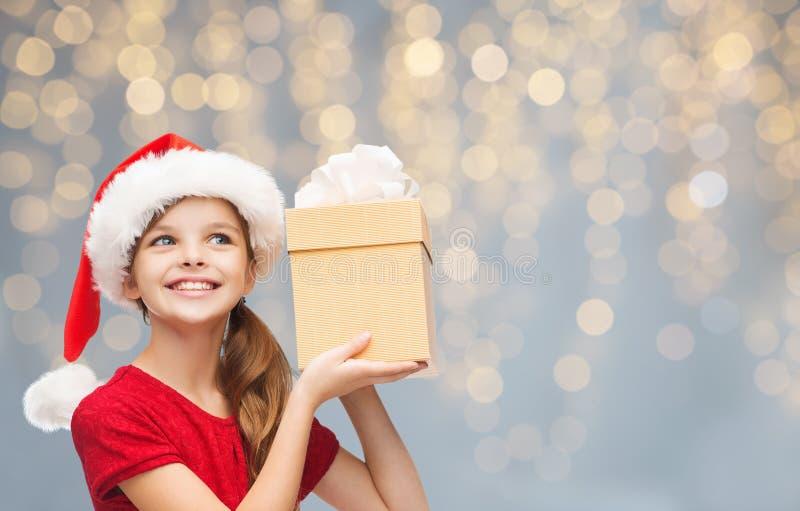 Fille de sourire dans le chapeau de Santa avec le boîte-cadeau de Noël image libre de droits
