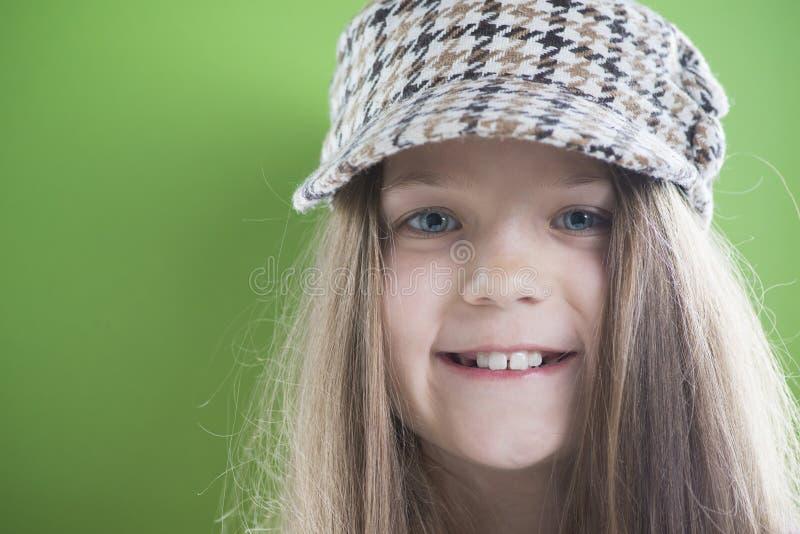 Fille de sourire dans le chapeau fait une pointe image stock