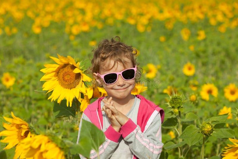 Fille de sourire dans le domaine des tournesols image stock