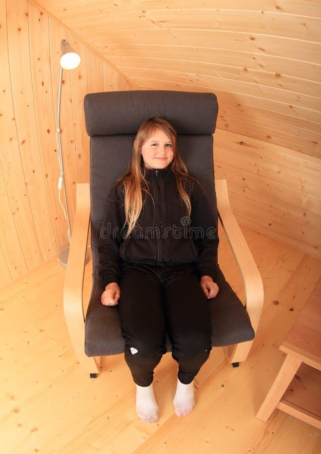 Fille de sourire dans le fauteuil image stock