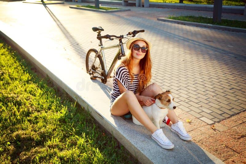 Fille de sourire de hippie avec l'animal familier et le vélo en été photos stock