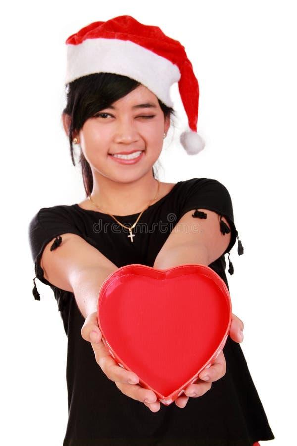 Fille de sourire de Noël donnant le coeur photo libre de droits