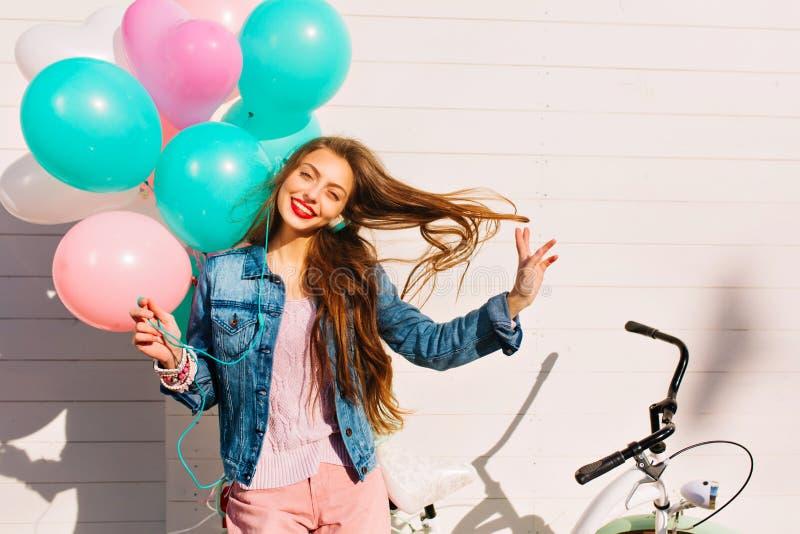 Fille de sourire drôle posant, jouant avec de longs cheveux et musique de écoute après tour de bicyclette de matin Assez femelle images libres de droits