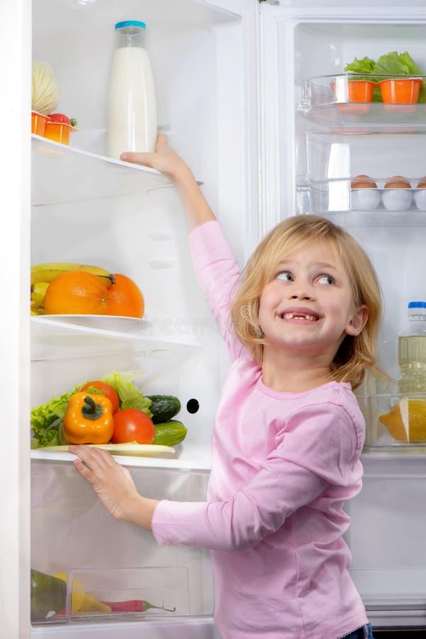 Fille de sourire drôle essayant de sélectionner la nourriture du réfrigérateur photographie stock libre de droits