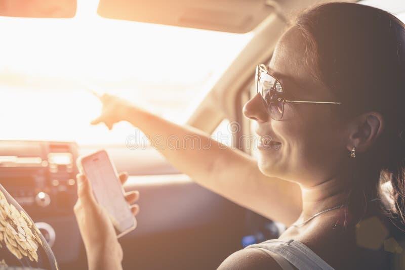 Fille de sourire employant l'application de navigateur de généralistes sur le smartphone pour diriger dans la voiture en vacances photos libres de droits