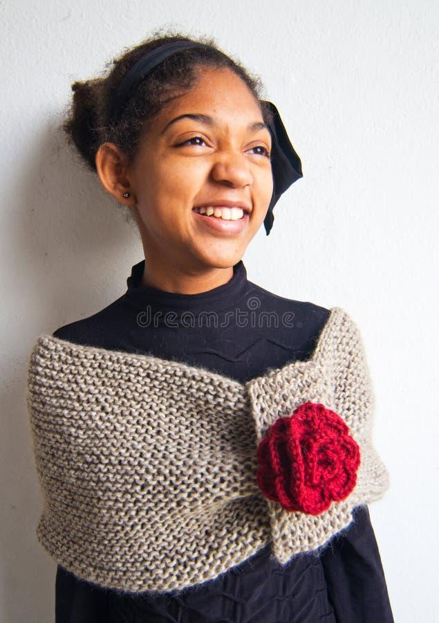 Fille de sourire enveloppée dans l'écharpe brun clair de laine avec la rose de rouge images libres de droits