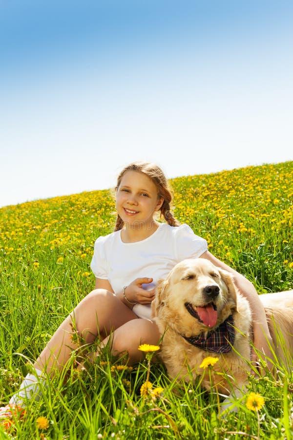 Fille de sourire et chien drôle se reposant sur l'herbe photos stock