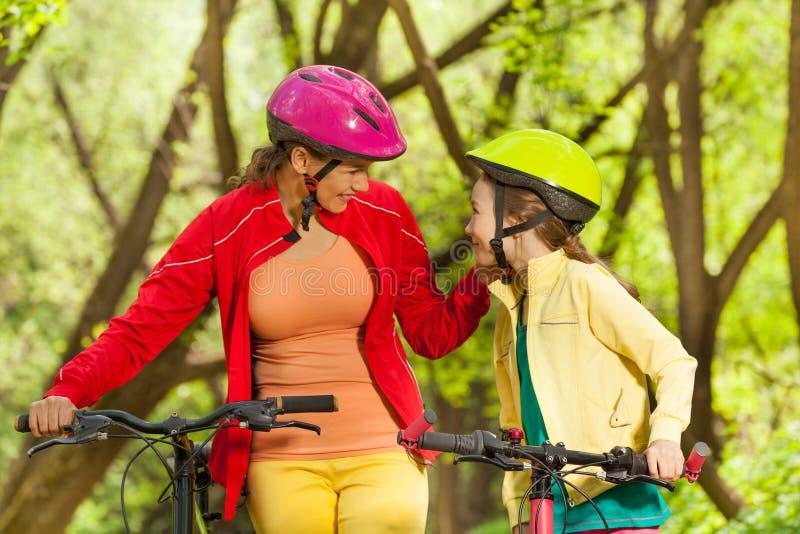 Fille de sourire et sa maman faisant un cycle au printemps le parc photos stock