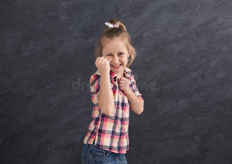 Fille de sourire faisant des gestes avec des poings sur le fond gris photo libre de droits