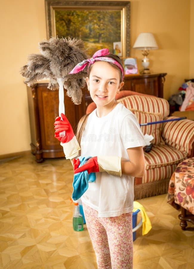 Fille de sourire faisant le nettoyage posant avec la brosse de plume image libre de droits
