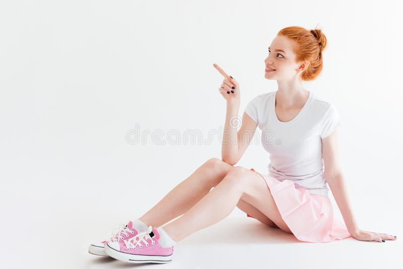 Fille de sourire de gingembre s'asseyant sur le plancher et se dirigeant loin image stock