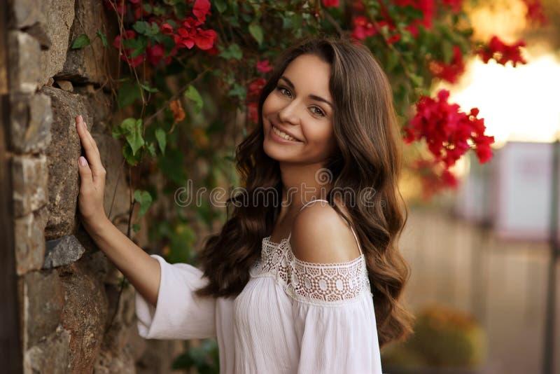 Fille de sourire heureuse contre des fleurs images libres de droits