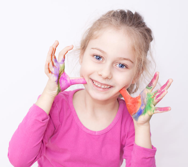 Fille de sourire heureuse d'enfant ayant l'amusement avec les mains peintes images stock