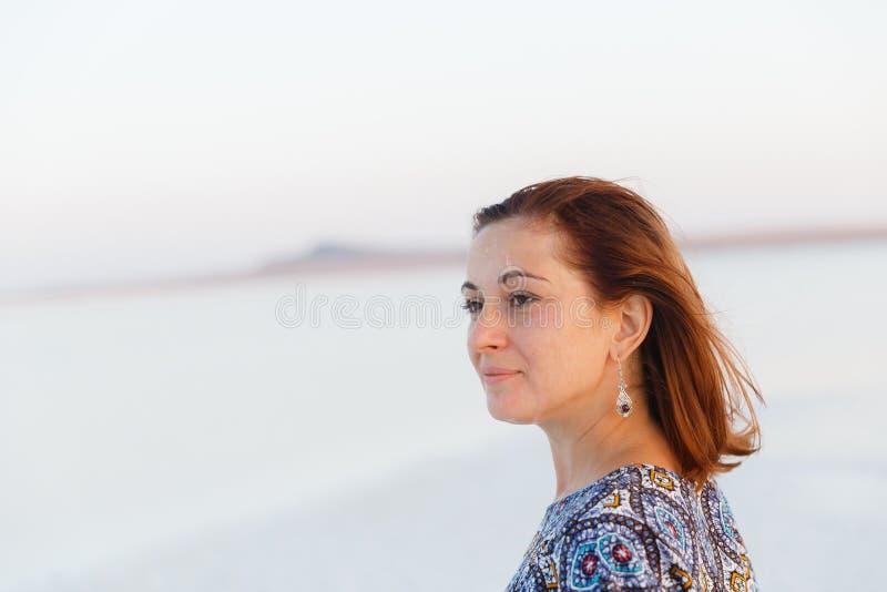 Fille de sourire heureuse dans le chapeau blanc appréciant le soleil, étendue de lac de sel de Bascunchak photographie stock libre de droits