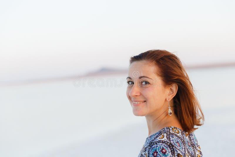 Fille de sourire heureuse dans le chapeau blanc appréciant le soleil, étendue de lac de sel de Bascunchak images stock