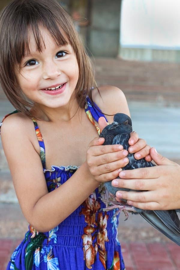 Fille de sourire heureuse de 4 ans tenant un oiseau dans des ses mains photos libres de droits