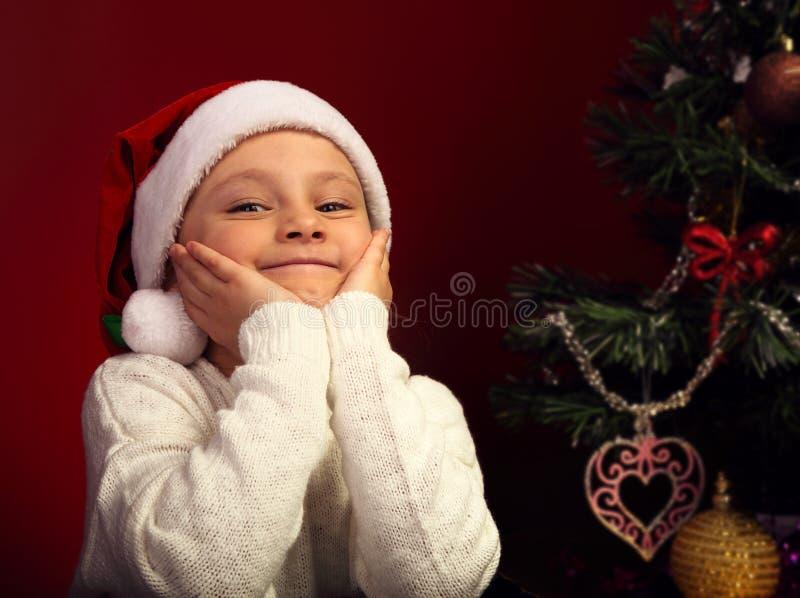 Fille de sourire heureuse mignonne d'enfant dans le chapeau du père noël de fourrure près du Chri image stock