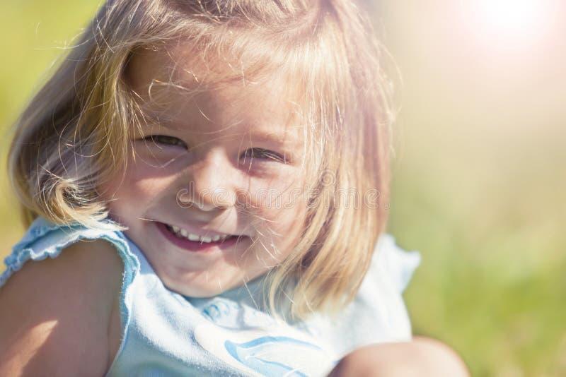 Fille de sourire heureuse s'asseyant dans l'herbe image libre de droits