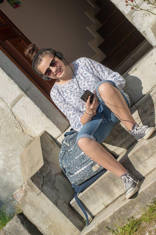 Fille de sourire de jeune adolescent s'asseyant sur les étapes, écoutant une musique image stock