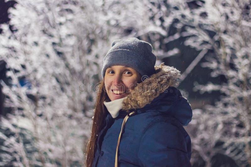Fille de sourire la nuit sur un fond des arbres en hiver image libre de droits