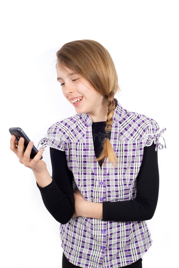 Fille de sourire lisant le message drôle à son téléphone portable d'isolement sur le blanc photos stock