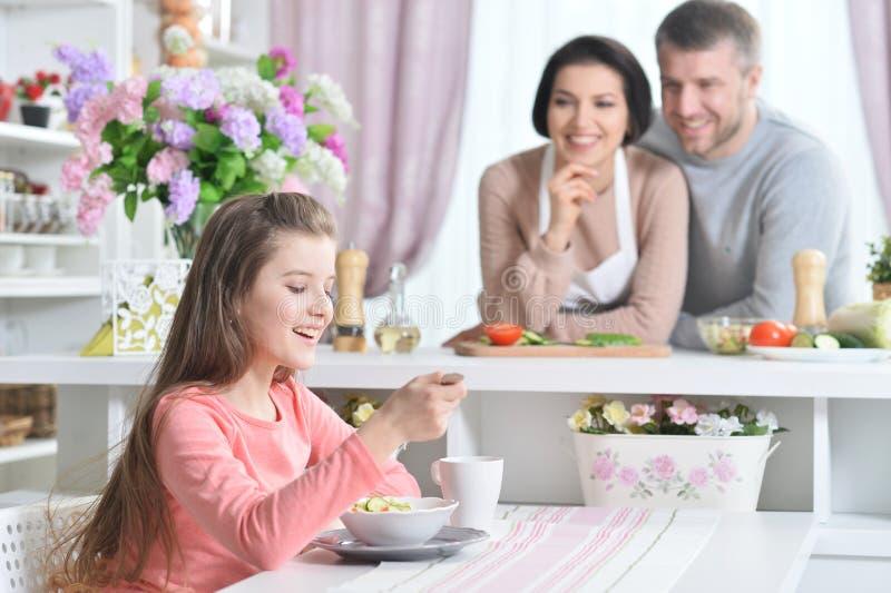 Fille de sourire mangeant à la cuisine photographie stock