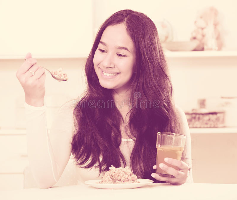 Fille de sourire mangeant des céréales et buvant du jus photos libres de droits