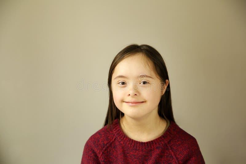 Fille de sourire mignonne de syndrome de Down sur le fond brun images stock
