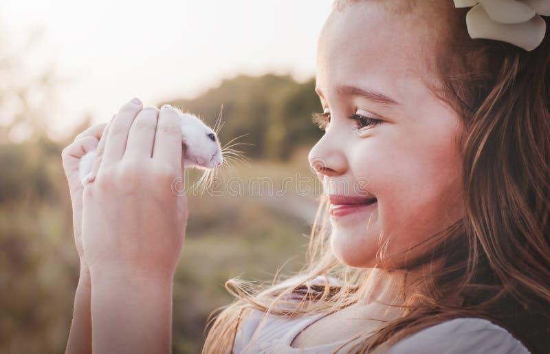 Fille de sourire mignonne tenant le hamster blanc - rétro regard images libres de droits