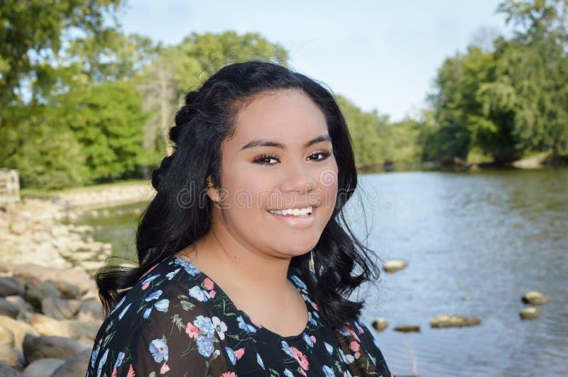 Fille de sourire par la rivière photographie stock libre de droits