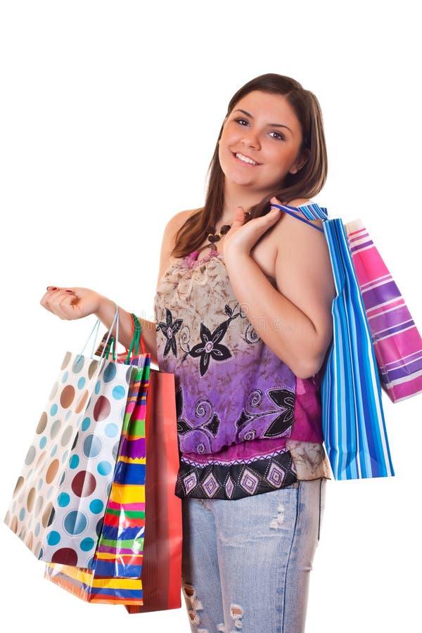 Fille de sourire restant avec les sacs à provisions colorés images libres de droits