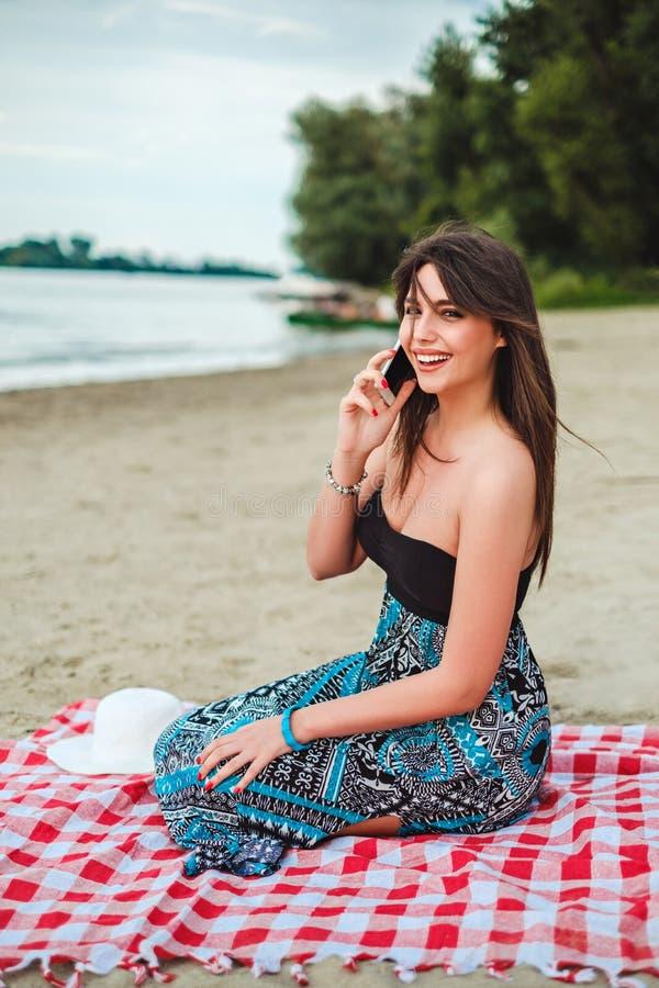 Fille de sourire s'asseyant à la plage et parlant au téléphone photographie stock libre de droits