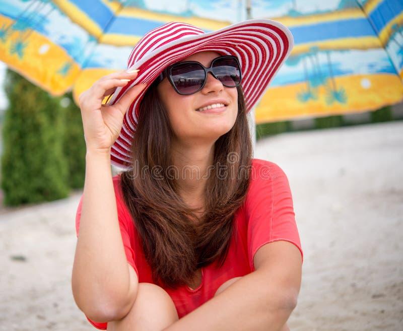 Fille de sourire s'asseyant sous le parapluie sur le sable photo stock