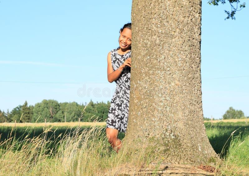 Fille de sourire se penchant sur l'arbre images stock