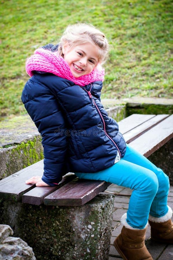 Fille de sourire sur un banc images stock
