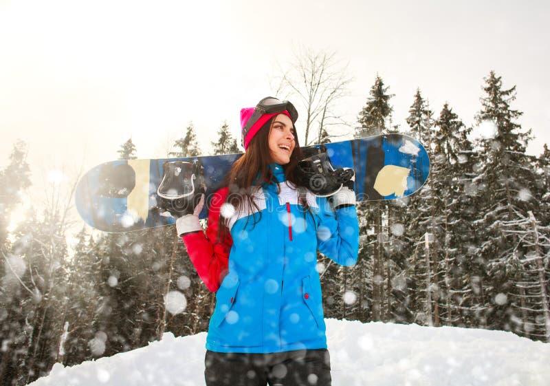Fille de sourire de surfeur en hiver en chutes de neige sur la forêt de pin photos stock