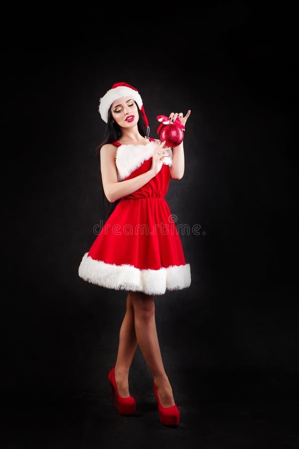 Fille de sourire tenant des boules d'un arbre de Noël de rouge Femmes sur la robe et le chapeau du ` s de Santa Aide du `s de San image stock