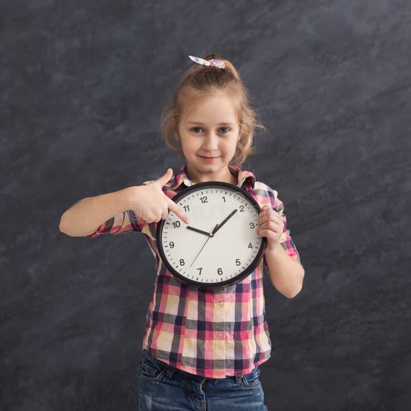 Fille de sourire tenant la grande horloge, se dirigeant là-dessus photo stock