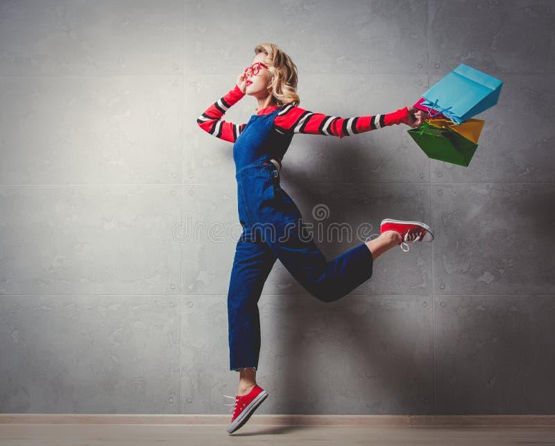 Fille de style dans des vêtements de jeans avec des paniers images libres de droits