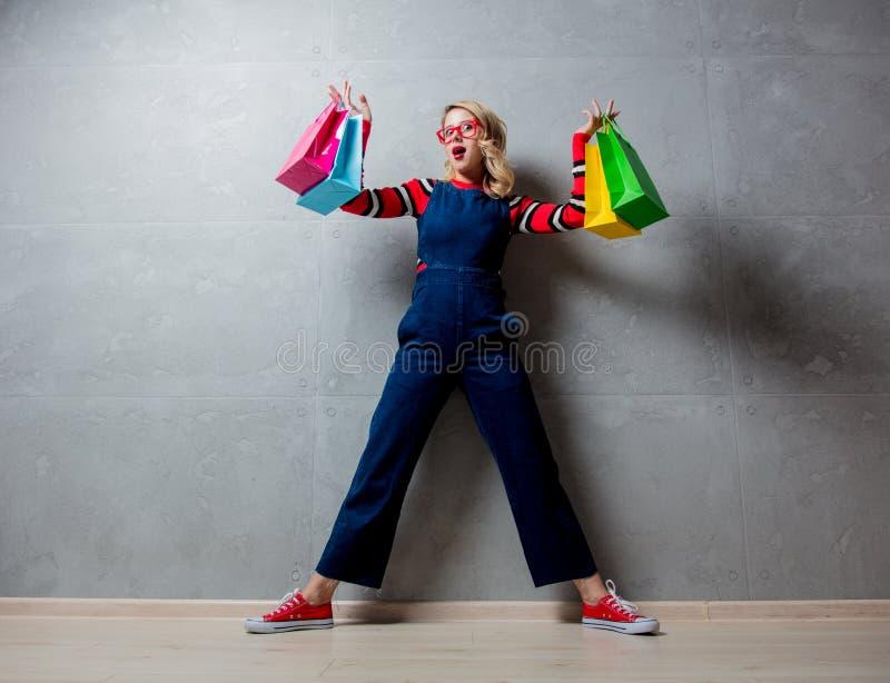 Fille de style dans des vêtements de jeans avec des paniers photos libres de droits
