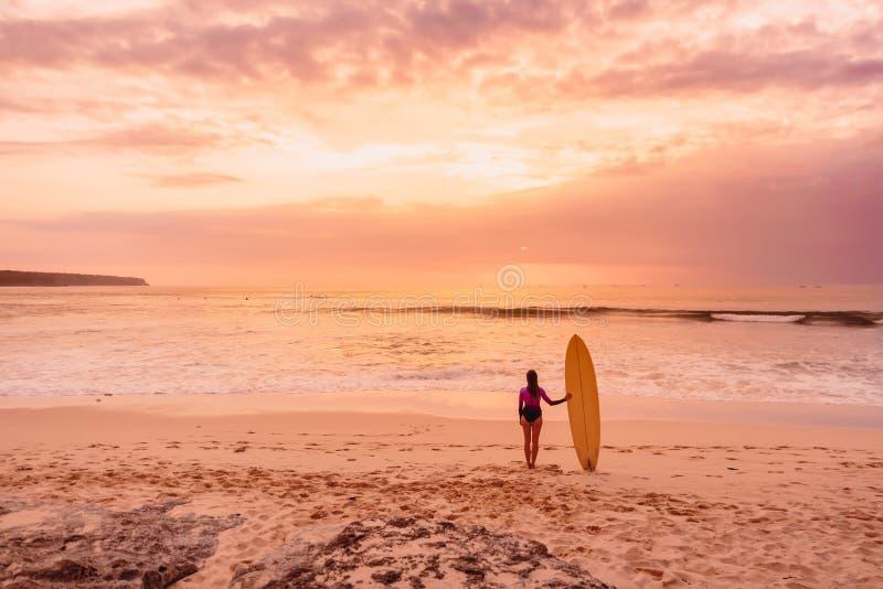 Fille de surfer avec la planche de surf à la plage Femme de surfer avec des couleurs de coucher du soleil ou de lever de soleil photographie stock libre de droits