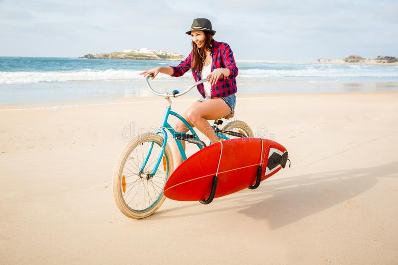 Fille de surfer montant un bicyicle photos stock