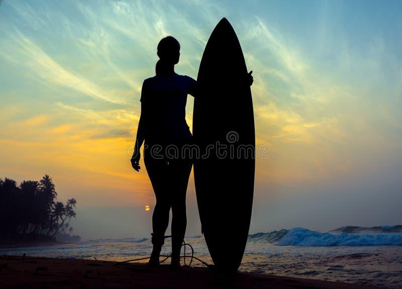 Fille de surfer surfant regardant le coucher du soleil de plage d'océan Silhouette W images stock