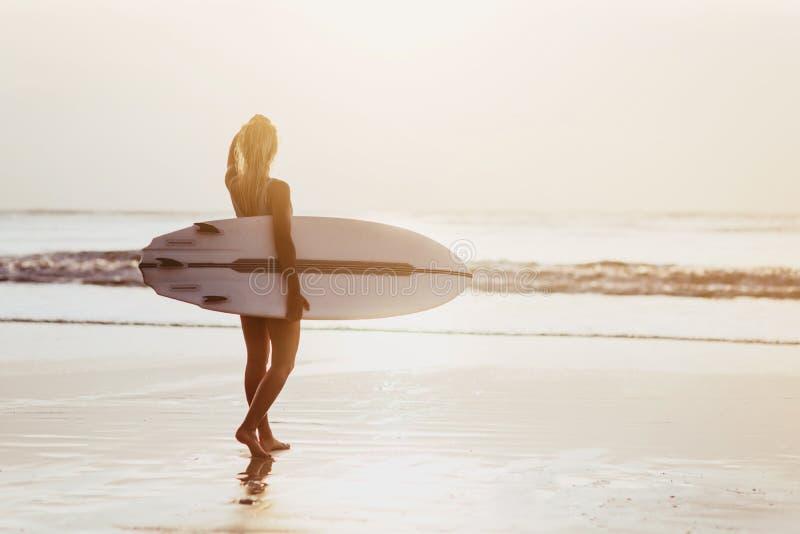 Fille de surfer surfant regardant le coucher du soleil de plage d'oc?an photos stock
