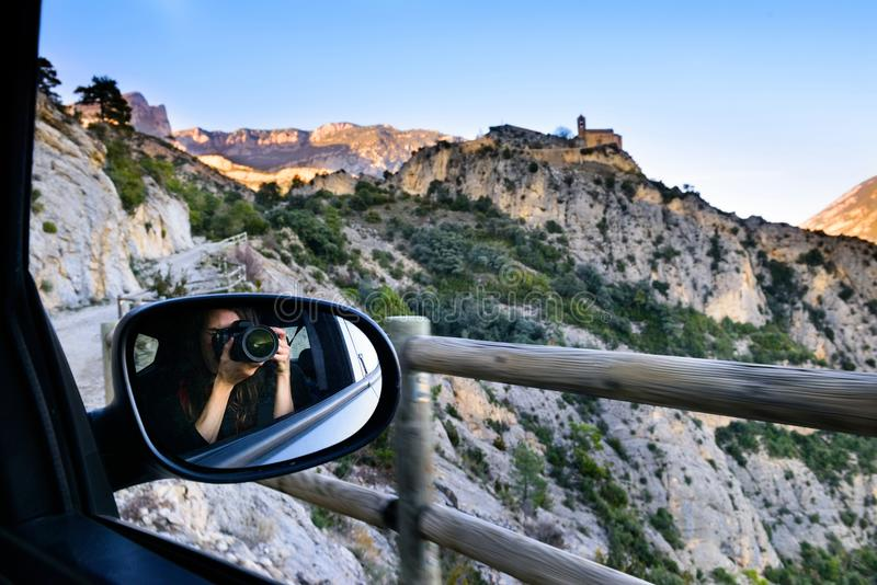 Fille de touristes en voyage, photographiant le paysage de montagne et un château médiéval photo libre de droits
