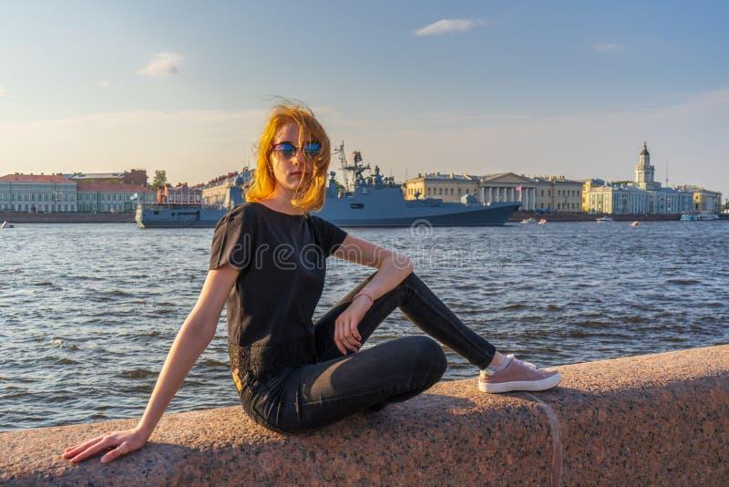 Fille de touristes de l'adolescence rousse sur le remblai de rivière de Neva posant contre les navires de guerre et l'ensemble ar photo stock