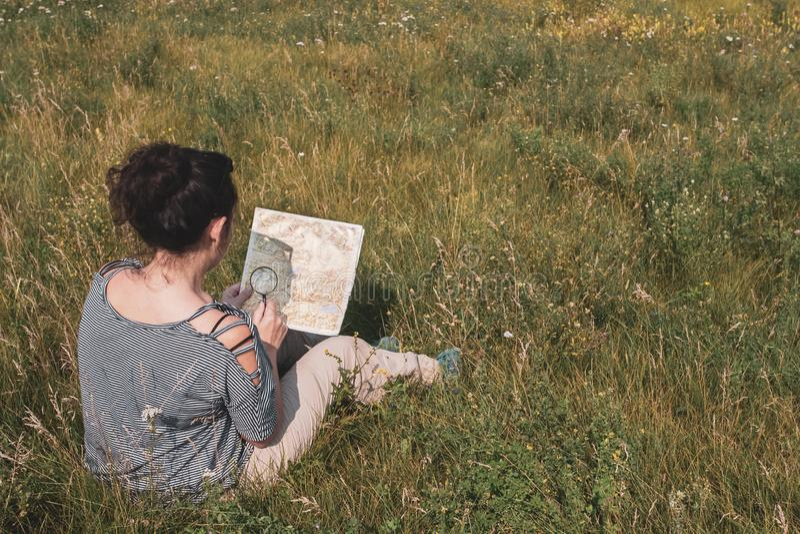 Fille de touristes s'asseyant dans l'herbe et regardant une carte avec une loupe à disposition images stock