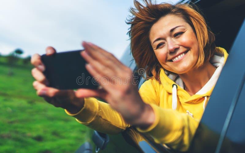 Fille de touristes de sourire dans une fenêtre ouverte d'une voiture automatique prenant le selfie de photo au téléphone intellig images stock