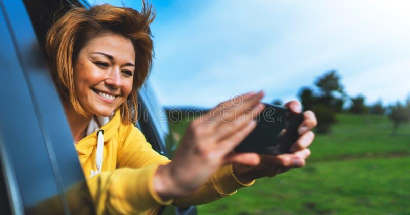 Fille de touristes de sourire dans une fenêtre ouverte d'une voiture automatique prenant le selfie de photo au téléphone intellig image stock